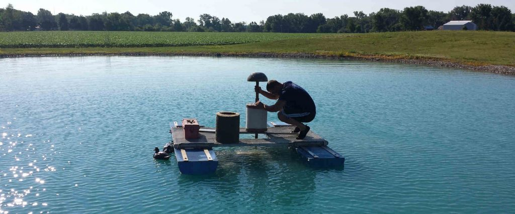 Aquatek Water Technician changing a pond filter for a customer who has a Pond Water Treatment System.