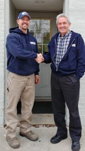 Brandon Schindler, current owner, and Bill Fortier, former owner shake hands in front of Aquatek Water Conditioning.